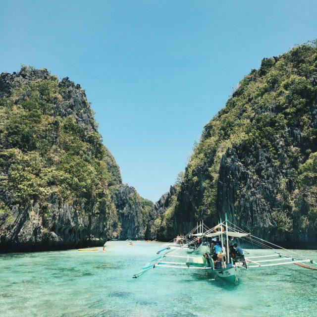 3 asiatiske robåde der sejler rundt i azurblår hav mellem 2 klippevægge