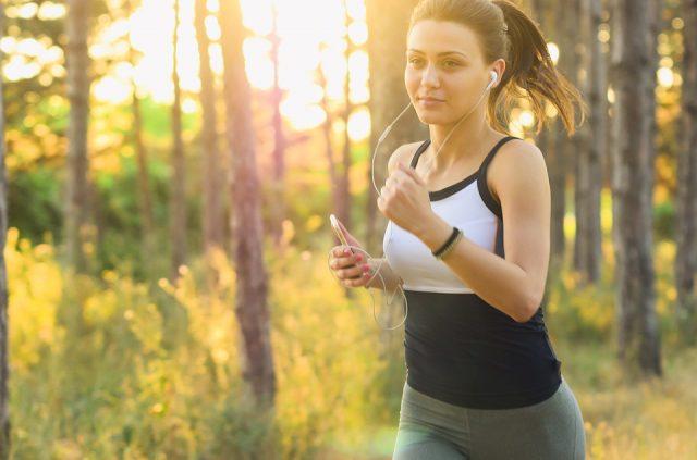 Kvinde der løber i skoven i solskin
